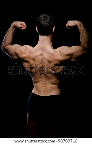 Portrait of strong back of a young muscular athletic man against dark background - stock photo