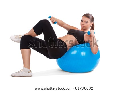 Portrait of strong girl lifting dumbbells on fitball - stock photo