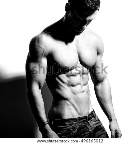 Portrait of strong healthy handsome Athletic Man Fitness Model posing near white wall