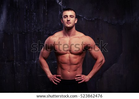 Portrait of strong healthy male model standing with hands on hips showing his reliefed body