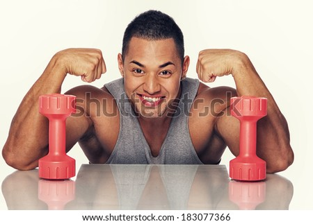Portrait of strong man posing in studio with dumbbells - stock photo