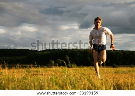 Portrait of strong man running and looking at camera - stock photo