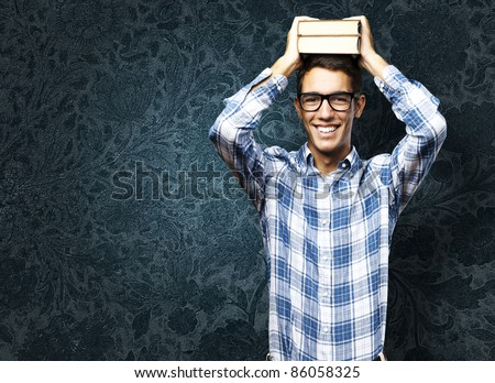 portrait of student with books on head against a grunge background - stock photo