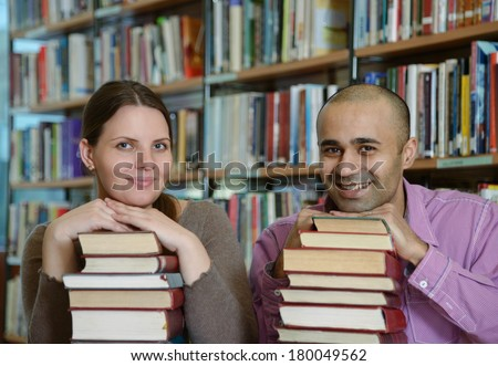 Portrait of students of different nationalities leaning their chins on piles of books in Bergen city library - stock photo