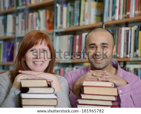 Portrait of students of different nationalities leaning their chins on piles of books in Bergen city library