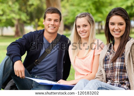 Portrait of students studying together while sitting in a park - stock photo