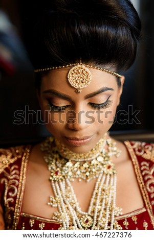 Portrait of stunning Indian bride with gold jewerly in her hair and on her neck