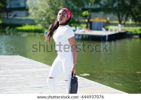 Portrait of stylish african american girl, wear on white clothes, with bag on hand against pier of lake. Street fashion of young black people.