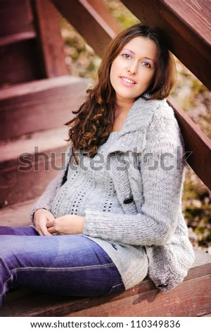 portrait of stylish autumn pregnant woman in warm sweater sitting on stairs - stock photo