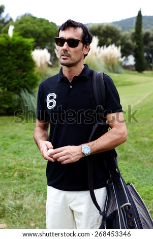 Portrait of stylish golfer man in glasses standing on beautiful golf course looking away, handsome brunette hair man with golf bag on shoulder holding ball in the hands