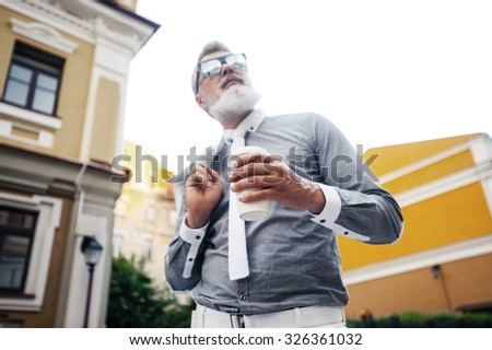 Portrait of stylish handsome adult man with beard standing outdoors. Man holding cup of coffee, wearing glasses and tie. Focus on cup - stock photo