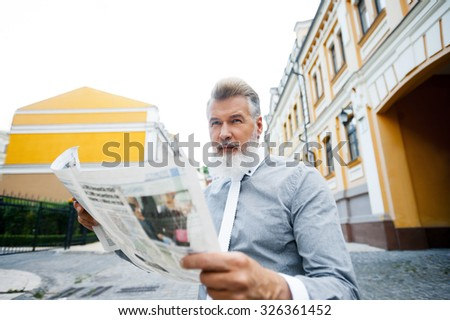 Portrait of stylish handsome adult man with beard standing outdoors. Man holding newspaper and wearing tie - stock photo
