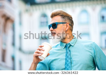 Portrait of stylish handsome adult man with beard standing outdoors. Man wearing glasses and holding cup of coffee - stock photo