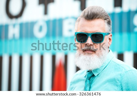 Portrait of stylish handsome adult man with beard standing outdoors. Man wearing glasses and looking at camera - stock photo