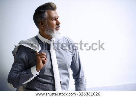 Portrait of stylish handsome adult man with beard standing outdoors. Man wearing tie and holding jacket - stock photo
