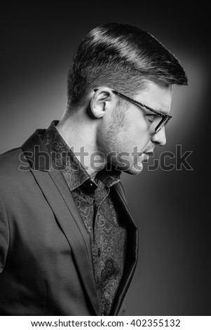 Portrait of stylish handsome young man with bristle . Man wearing jacket and shirt - stock photo
