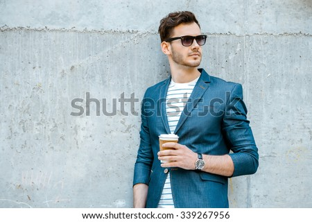 Portrait of stylish handsome young man with bristle standing outdoors and leaning on wall. Man wearing jacket, sunglasses, shirt and holding cup of coffee - stock photo