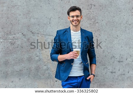Portrait of stylish handsome young man with bristle standing outdoors. Man wearing jacket and shirt. Smiling man with glasses holding cup of coffee and leaning against wall - stock photo