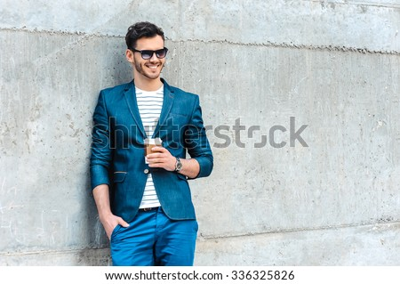 Portrait of stylish handsome young man with bristle standing outdoors. Man wearing jacket and shirt. Smiling man with sunglasses holding cup of coffee and leaning against wall - stock photo