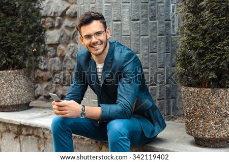 Portrait of stylish handsome young man with bristle standing outdoors. Man wearing jacket and watch. Man with glasses cheerfully smiling and using mobile phone - stock photo