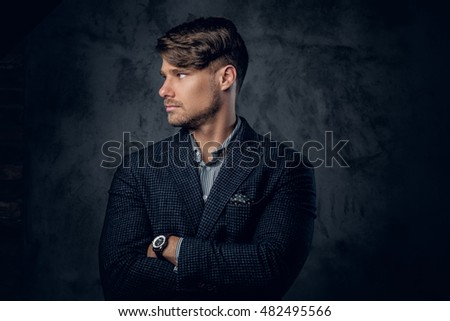 Portrait of stylish male in a suit on grey background.