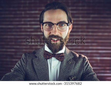 Portrait of stylish man against brick wall