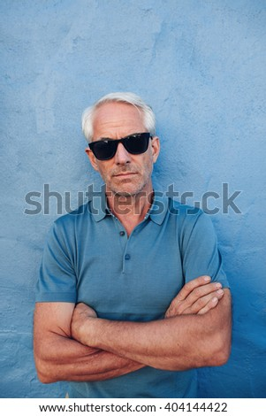 Portrait of stylish mature man wearing sunglasses standing with his arms crossed against blue background - stock photo