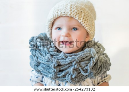 portrait of stylish pretty nice smiling baby girl in wool snood and hat, tall boots and modern dress staying on white background and wooden floor watching aside - stock photo