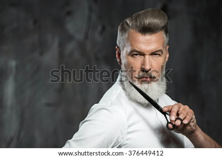 Portrait of stylish professional hairdresser with beard. Man wearing shirt, looking aside and holding scissors near his beard - stock photo
