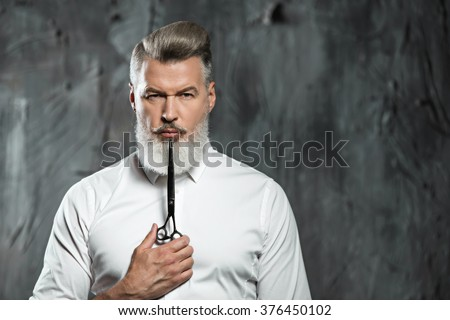 Portrait of stylish professional hairdresser with beard. Man wearing shirt, looking at camera and holding scissors near his beard - stock photo