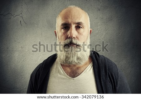 portrait of stylish senior man with grey-haired beard over grey background - stock photo