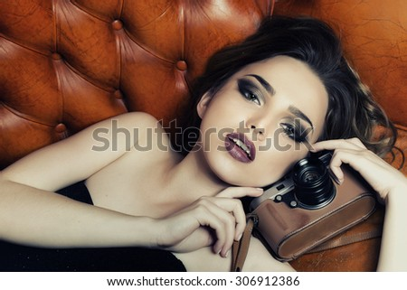 Portrait of stylish sexual young lady with bright makeup in black dress without shoulder-straps looking forward lying on leather brown royal sofa holding photographic camera, horizontal picture - stock photo