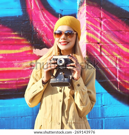 Portrait of stylish smiling girl with old retro camera having fun outdoors against the colorful graffiti wall - stock photo