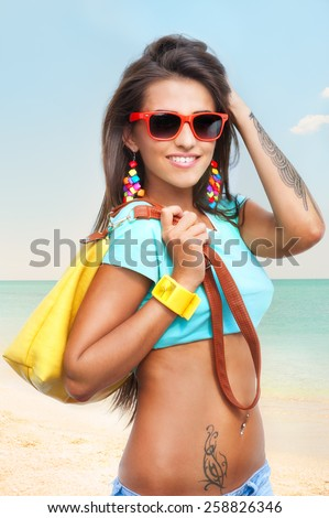 Portrait of stylish smiling young woman in sunglasses with yellow bag on sunny beach - stock photo