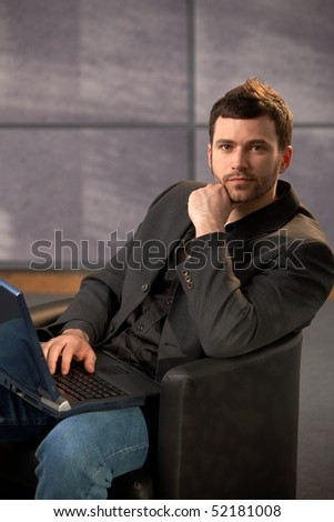 Portrait of stylish young businessman sitting in armchair working on laptop computer in office, looking at camera.