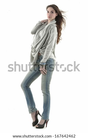 Portrait of stylish young model in fashion jeans - white background. Fashion model posing at studio - stock photo