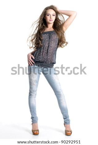 Portrait of stylish young model in fashion jeans - white background.  Fashion model posing at studio