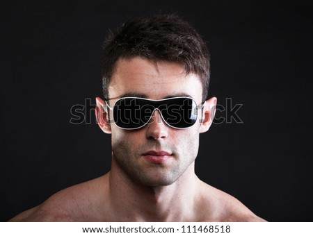 Portrait of stylished young man wearing sunglasses black background