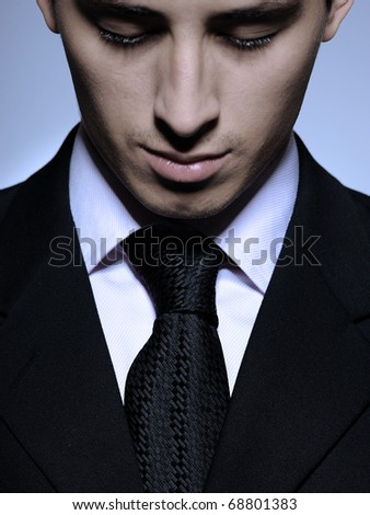 Portrait of succesful  business man in formal suit and black tie looking down. gray background - stock photo