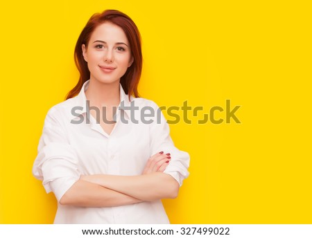 Portrait of success redhead woman on yellow background - stock photo