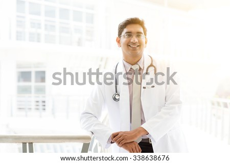 Portrait of successful Asian Indian medical doctor smiling and standing outside hospital building, beautiful golden sunlight at background. - stock photo