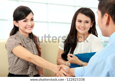 Portrait of successful business colleagues shaking hands after interview
