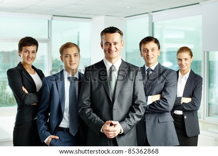 Portrait of successful business group looking at camera with confident man at foreground