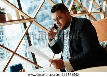 Portrait of successful business man talking on smart phone inside coffee shop. Attractive adult man in suit talking on the phone and looking on paper