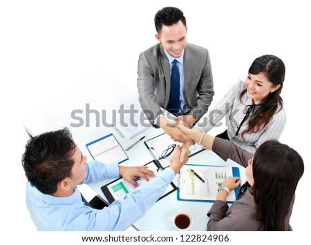 Portrait of successful business team shaking hands with eachother in the office - stock photo