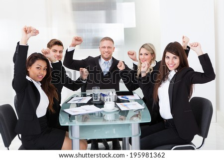 Portrait of successful business team with arms raised sitting at desk at office
