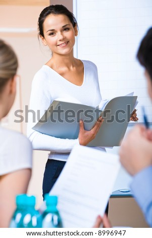 Portrait of successful business woman holding a folder and looking at her colleagues at meeting - stock photo