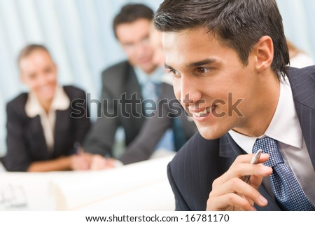 Portrait of successful businessman and business team at office meeting