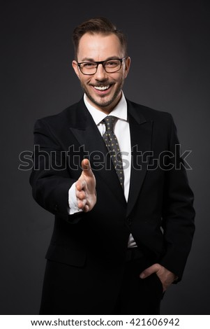 Portrait of successful businessman giving his hand for handshaking. Happy smiling man in glasses looking at camera. - stock photo