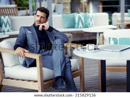 Portrait of successful businessman in a luxury expensive suit resting at cafe after hard work day and look pensive,rich entrepreneur waiting for a meeting with colleague at open air restaurant terrace - stock photo